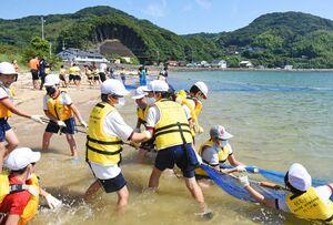 海に漬かりながらも必死に網を引く児童たち=唐津市の幸多里の浜