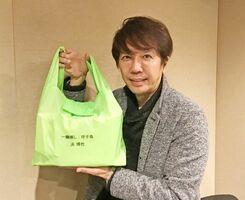 自身の話題曲のタイトル入りマイバッグを持つ歌手・浜博也