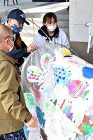 園児たちが描いた魚の絵を貼り合わせて、こいのぼりを作る古賀百葉さん(右)ら天山ものづくり塾のメンバー=小城市のゆめぷらっと小城