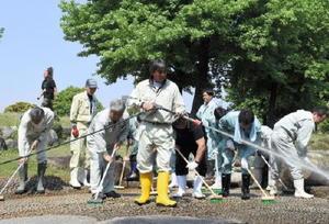 仕事用の電動工具などを使って水遊び場を清掃する参加者=佐賀市の県立森林公園
