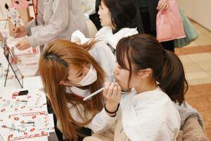 美容専門学校による「春カラーリップ体験」に参加する来場者=佐賀市天神のロイヤルチェスター佐賀