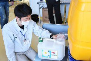 施設の職員が持参したタンクに次亜塩素酸水を入れる市職員=唐津市二タ子の市健康サポートセンターさんて