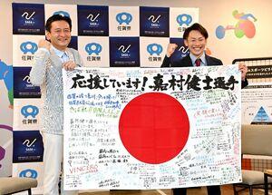応援メッセージが書かれた旗を手にする嘉村健士選手(右)と山口祥義知事=佐賀市の佐賀県庁