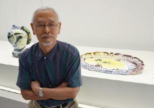「優美な縁飾り付の楕円皿」(右後方)で書道に近い感覚を覚えたという成冨宏さん=佐賀市の県立美術館
