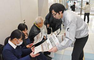 伊万里高校の甲子園出場を伝える号外を手に取る学生ら=伊万里市の伊万里駅