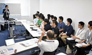 木村情報技術の担当者(左)から、AI(人工知能)を使ったシステムなどについて話を聞く参加者ら=佐賀市の同社