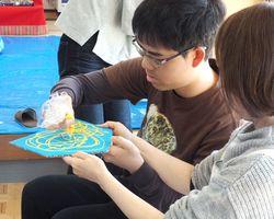 ビニール袋から色を混ぜた木工用接着剤を絞り出し、絵を描く参加者