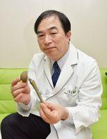 抗菌性を高めた人工股関節を手にする馬渡正明教授=佐賀市の佐賀大学鍋島キャンパス