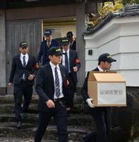 道仁会の関係住宅での家宅捜索を終え、段ボール箱を抱えて出る福岡、佐賀両県警の捜査員たち=5日午後2時40分ごろ、久留米市上津町
