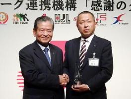 日本トップリーグ連携機構の川淵三郎会長(左)からトロフィーを受け取ったレッドトルネードの藤瀬輝GM=19日夜、東京・高輪のグランドプリンスホテル新高輪