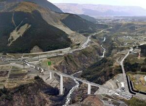 開通した新阿蘇大橋(手前)。奥は2016年の熊本地震で大規模に崩壊した斜面=7日午後、熊本県南阿蘇村(共同通信社ヘリから)