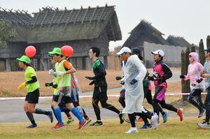 目標タイムを設定し、ペース配分を確認しながら走る参加者=吉野ケ里歴史公園