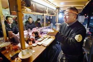 来店した客と話す屋台「かじしか」の店主下村克彦さん=23日夜、福岡市