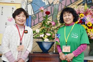 自宅で育てた花を持ち寄って校内に飾っている蘭信子さん(右)と岸川イツヱさん=小城市牛津町の砥川小