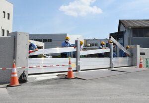 防災訓練で正面玄関に浸水を防ぐアルミゲートを設置する職員=大町町の佐賀鉄工所大町工場