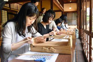 竹べらを糸のような和紙に通していく参加者たち=佐賀市松原の旧福田家