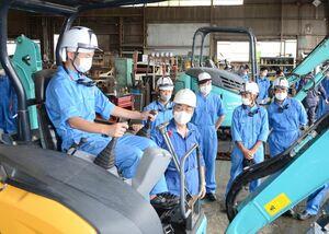 職場体験学習でショベルカーに試乗し、アームの動作を確認する生徒たち=鹿島市の鹿島機械工業