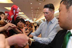 羽田空港に到着し、出迎えたファンにサインで応じるサガン鳥栖のフェルナンド・トーレス=15日午前11時25分ごろ、東京都の羽田空港