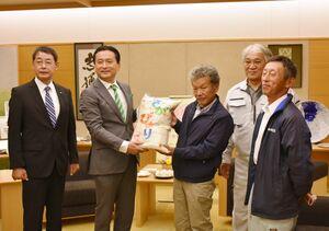営農再開後に初めて収穫した米を山口知事(左から2人目)に贈呈した農家の灰塚晃幸さん(同3人目)ら=佐賀県庁