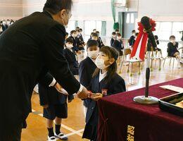 梶原校長(左)から教科書を受け取る新入生=佐賀市の東与賀小