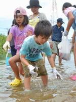 川に放たれたニジマスを捕まえる参加者=上峰町の切通川