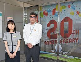 「佐賀ターミナルビル」の木下英子さん(左)と高尾茂行さん。自動ドアにも、開港20年を祝うラッピングを施している=佐賀市川副町の佐賀空港