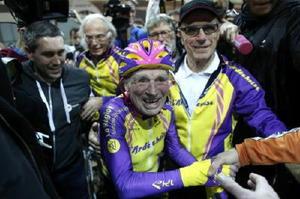 4日、パリ郊外の自転車競技場で1時間に22・547㌔を走り、祝福される105歳のロベール・マルシャンさん(中央)(AP=共同)
