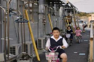 熊本地震の被災者が避難生活を送る仮設住宅団地。夕暮れ時に子どもたちが自転車に乗って遊んでいた=13日夕、熊本県益城町