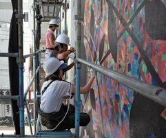 足場に乗って壁に色を塗る参加者