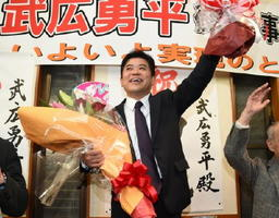 当選が確実となり、花束を手に笑顔を見せる武広勇平氏=12日午後10時18分、三養基郡上峰町坊所の事務所