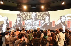 幕末維新期の佐賀の偉業や偉人の活躍を紹介する映像に見入る来場者=佐賀市城内の幕末維新記念館