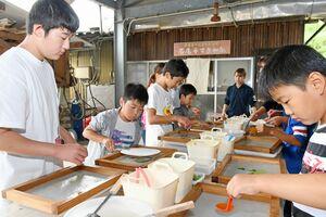 和紙に色を付けたり、葉などの飾り付けをしたりする子どもたち=佐賀市の和紙工房「名尾手すき和紙」