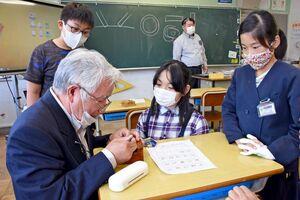 ものづくりマイスターから印鑑の彫り方を学ぶ児童たち=唐津市の伊岐佐小