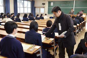 大学入試センター試験の初日の試験が行われた佐賀県内の試験会場。係員から受験生に問題用紙が配布される=佐賀市の佐賀大学本庄キャンパス
