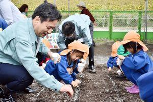 ポピーの種まきをする山口知事(左)と園児たち=佐賀市川副町