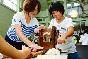 専用の道具で綿の種を取り除く体験をする親子=佐賀市城内の岡田三郎助アトリエ