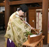 包丁に見立てた矢でブリに切れ目を入れる「調理の儀」=佐賀市の佐嘉神社