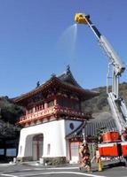 国重文の楼門への延焼を防ぐため、はしご車から放水する訓練=武雄市の武雄温泉