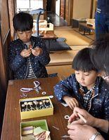 佐賀錦を飾りにしたキーホルダーを作る子どもたち=佐賀市松原の旧福田家