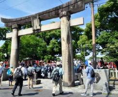 昭和30年~50年代に撮影された写真と、現在の鳥居から見える風景を見比べる参加者=佐賀市の松原神社