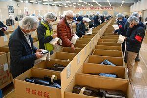 入札会でノリの色つやなどを確認する流通業者ら=佐賀市の佐賀海苔共販センター