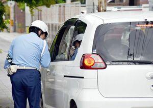 横断歩道付近での一時停止など注意を呼び掛ける警察官=佐賀市松原