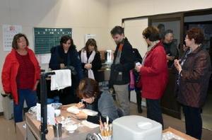 絵付け作業を視察する海外の旅行会社関係者=伊万里市大川内町の畑萬陶苑