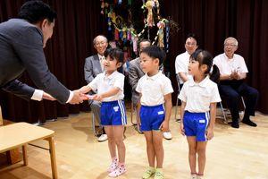 本を受け取る園児代表の子どもたち=鳥栖市のあいりす保育園