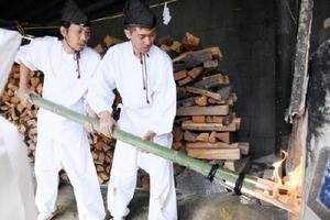 炎を登り窯に入れる窯元関係者=伊万里市大川内山の鍋島藩窯公園