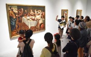 ギャラリートークで、バロック絵画を解説する画家の小木曽誠さん(中央)=佐賀市の県美術館