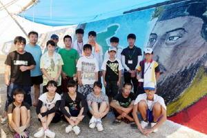 日韓友好の願いを込めて防波堤に絵を描き上げた児童、生徒たち=唐津市鎮西町の加唐島