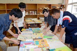 将来なりたいものを描いた絵を見ながら、当時の思い出を語り合う大山小の卒業生たち=有田町の同校