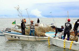 助け合いながら海底にササ竹を突き刺す漁業者=佐賀県沖の有明海