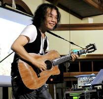 特注したベフニックギターでオリジナルソング「アジサイ」を演奏する小倉博和さん=佐賀市柳町の浪漫座